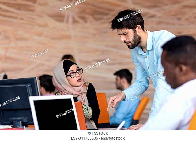 diverse college students using laptop and talking, learning exchanging ideas