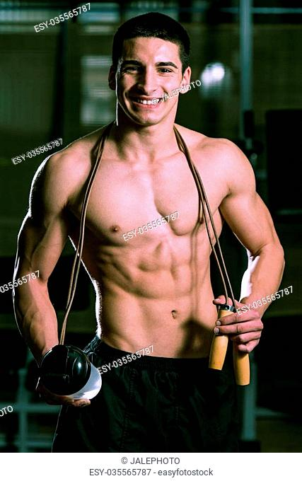 Handsome Muscular Man With Jumping Rope - Holding A Bottle Of Water In His Hand