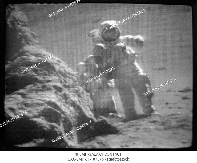 The two moon-exploring Apollo 17 crewmen are seen walking beside a large boulder during the third extravehicular activity (EVA) at the Taurus-Littrow landing...