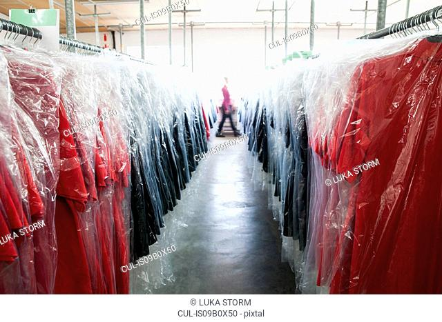 Diminishing perspective of garments on clothes rail in sewing factory