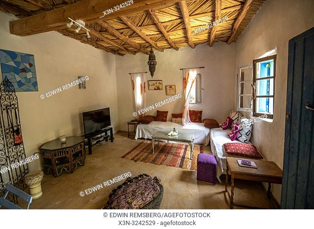 Interior of living room with thatch ceiling in traditional mud-brick built home in Tighmert Oasis, Morocco