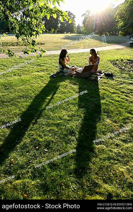 14 August 2021, Brandenburg, Neuhardenberg: Two young women sit with a picnic basket on a meadow in Neuhardenberg Castle Park