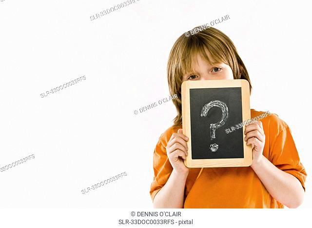 Boy holding question mark on chalkboard