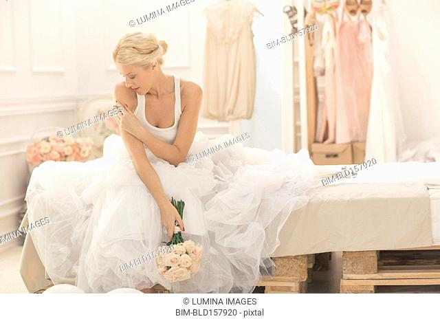 Pensive bride sitting with bouquet on bed