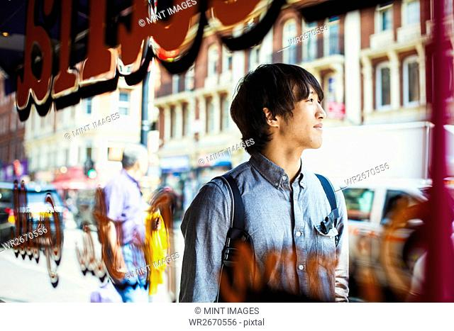 Young Japanese man enjoying a day out in London, walking past a shop window