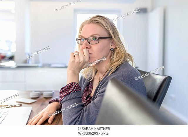 Woman is sitting thoughtfully at the kitchen table