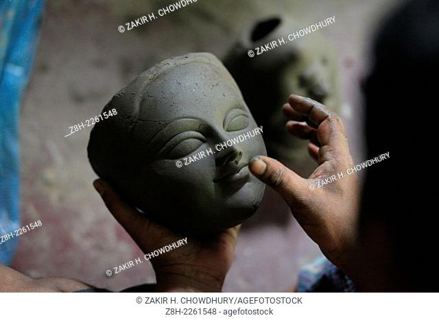 Bangladeshi artist works on a clay idol of the Hindu Goddess Durga in preparation for the forthcoming Hindu festival Durga Puja in Old Dhaka