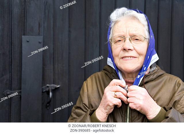 Frau in ihren Siebzigern bindet sich lachend ein Kopftuch unter dem Kinn zusammen