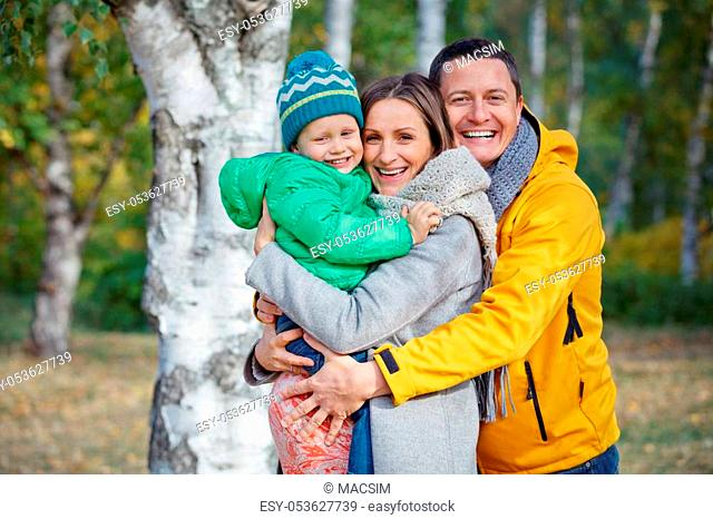 Happy family of three playing in autumn park
