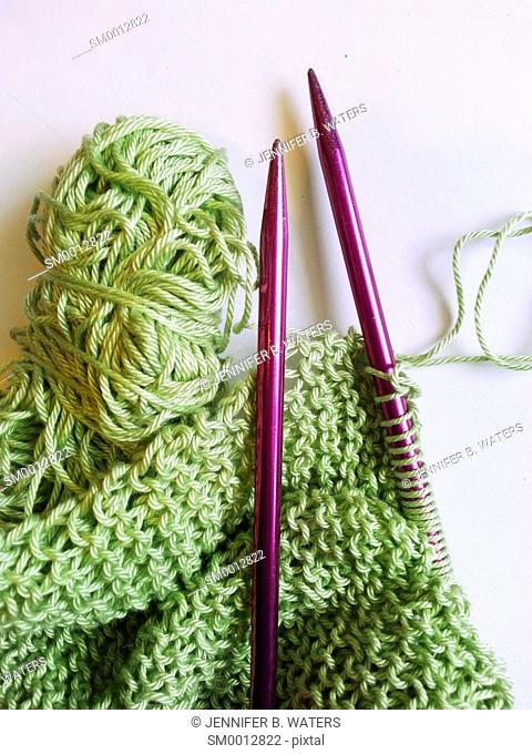Green yarn on knitting needles with a scarf in process