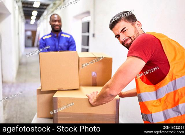 Zwei Arbeiter transportieren Pakete auf dem Schubwagen ins Warenlager der Spedition