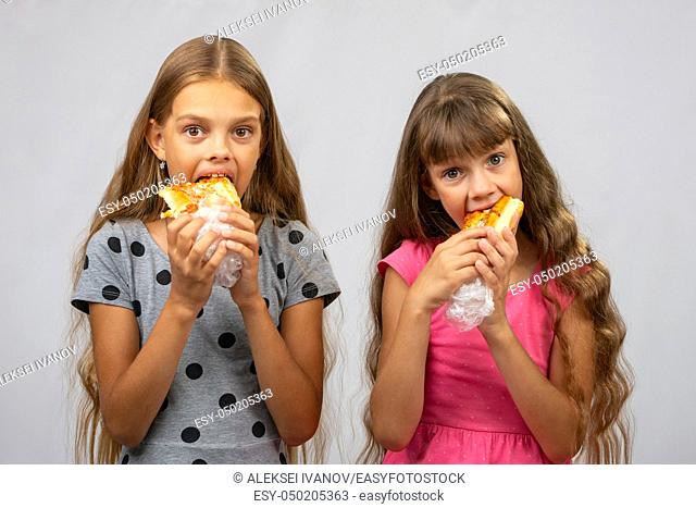 Two hungry girls eat bread, and look at the frame
