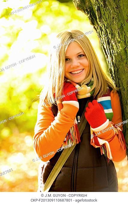 Happy blonde teenager girl autumn forest smiling fall tree