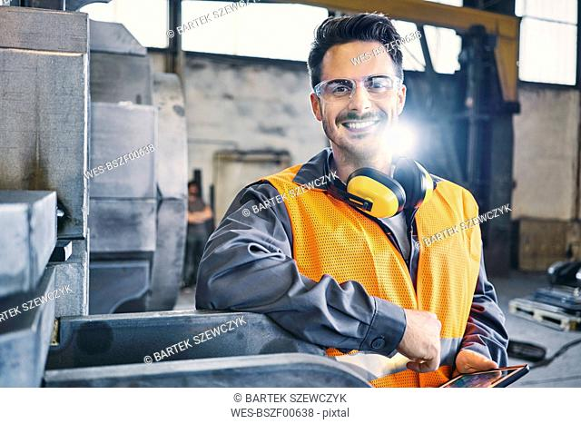 Portrait of smiling man wearing protective workwear and holding tablet in factory