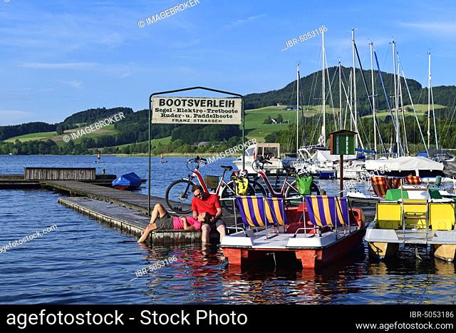Couple with electric bikes pauses on a landing stage at Lake Obertrumer See, Obertrum, Salzburger Seenland, Salzburger Land, Austria, Europe