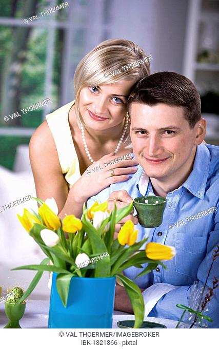 Young couple in the living room, tulips, Easter egg