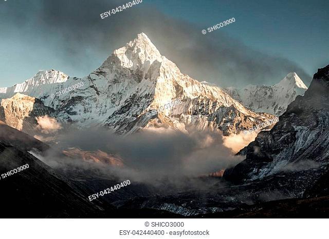 Ama Dablam mountain at sunset and blue sky. Sun illuminates slopes. Himalayan mountains, Nepal