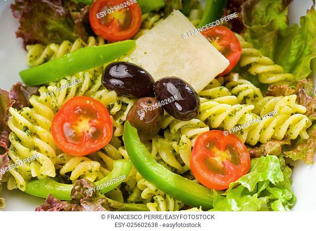 fresh healthy homemade italian fusilli pasta salad with parmesan cheese, pachino cherry tomatoes, black olives and mix vegetables