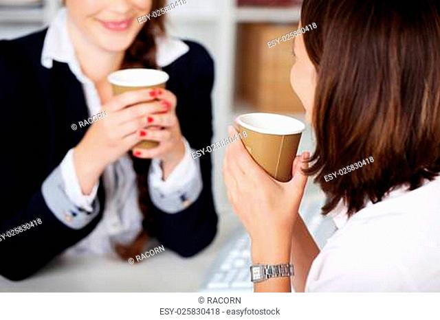 Office coffee break with two female colleagues sittng chatting over cups of coffee