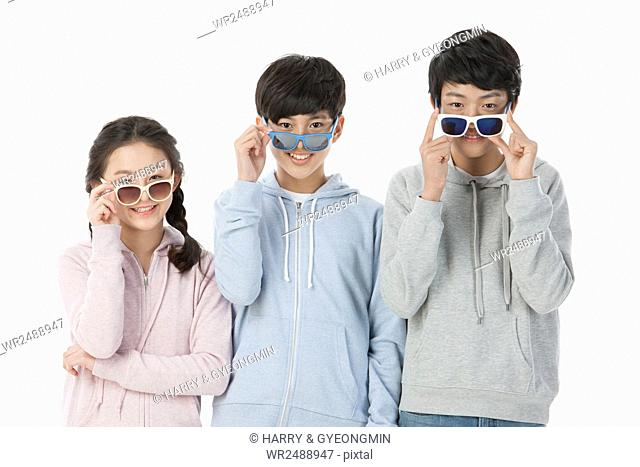 Portrait of three smiling teenagers in casual clothes wearing sunglasses