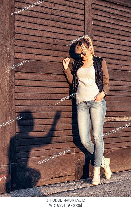 Young woman looking at silhouette of young man on wooden wall