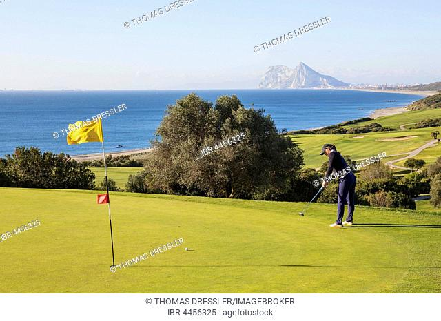 Golfer putting on green, La Alcaidesa Golf Resort with Mediterranean Sea and Rock of Gibraltar, Cádiz, Andalusia, Spain
