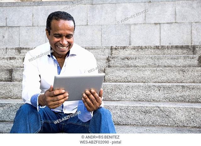 Portrait of smiling man sitting on stairs looking at tablet