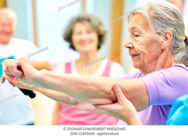 Senior bekommt Hilfestellung bei einer Übung mit Elastikband im Pilates Kurs
