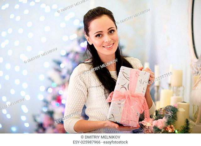 Young happy beautiful woman with gift boxes stands near Christmas tree in the room of the house. Merry Christmas and New Year