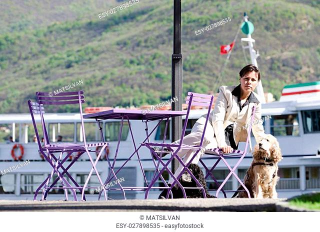 Woman sitting down in a patio with her dogs close to a lake and a passenger ship