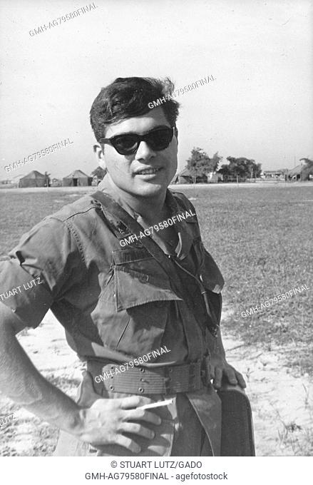 A United States Army serviceman posing with his hands on his hips, he is smiling and wearing sunglasses while standing on base, Vietnam, 1967