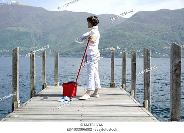 Woman scrubs the pier over the lake with cleaning equipment and snow-capped mountain in background