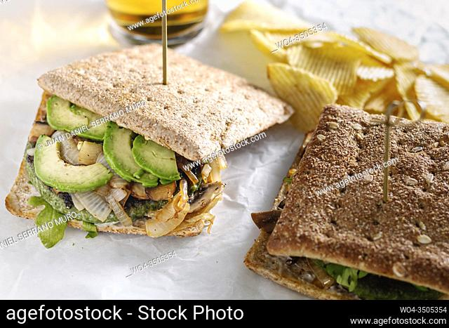 Seed bread sandwiches with avocado, grilled onion and arugula, chips as side dish in white paper