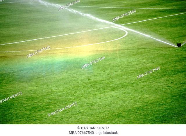 The green lawn of a football field with an irrigation system making a rainbow