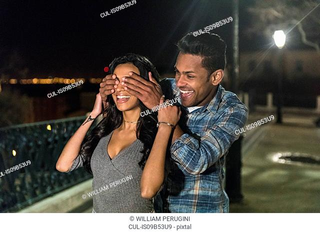 Couple in city at night, fooling around, man covering woman's eyes with hands, Lisbon, Portugal