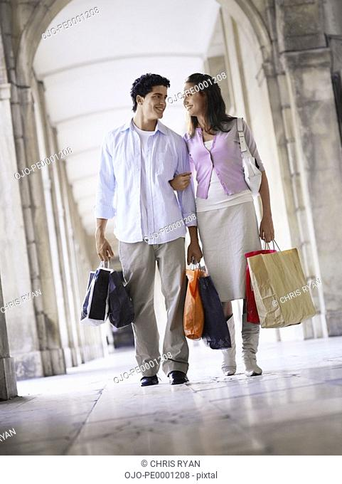 Young couple with shopping bags walking in an old European colonnade