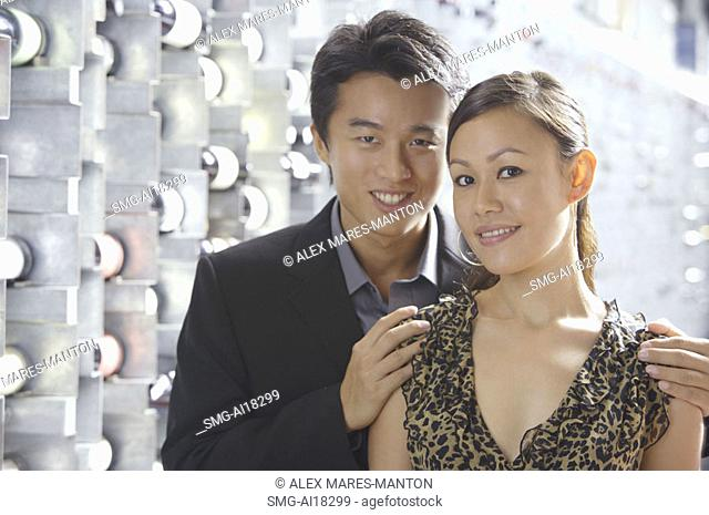 Couple standing in wine cellar, looking at camera, portrait