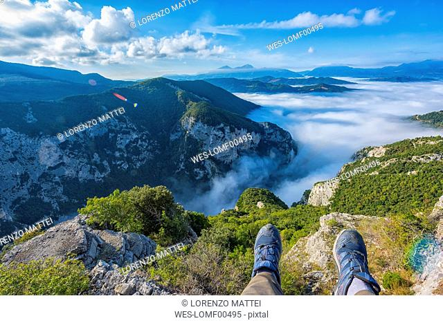 Italy, Marche, Apennines Mountains, Furlo Pass, feet of resting hiker on top of mountain