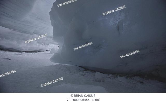 Tracking shot of man with snowboard walking in ice cave, Whistler, British Columbia, Canada