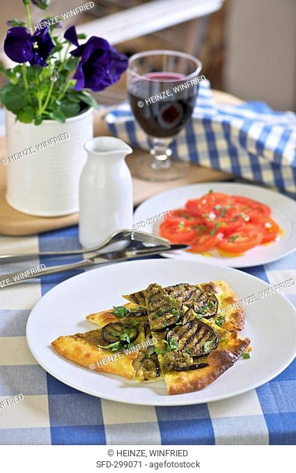 Aubergine pizza with pesto, tomato salad