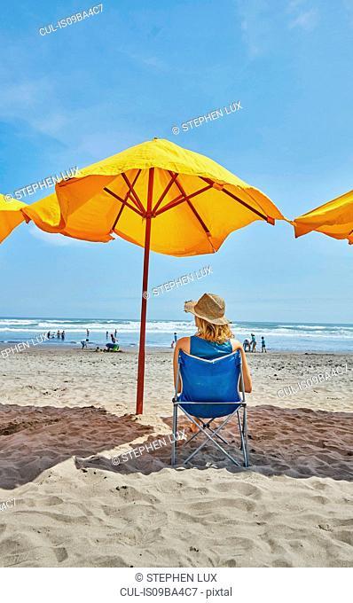 Rear view of female tourist sitting under beach umbrella, Camana, Arequipa, Peru