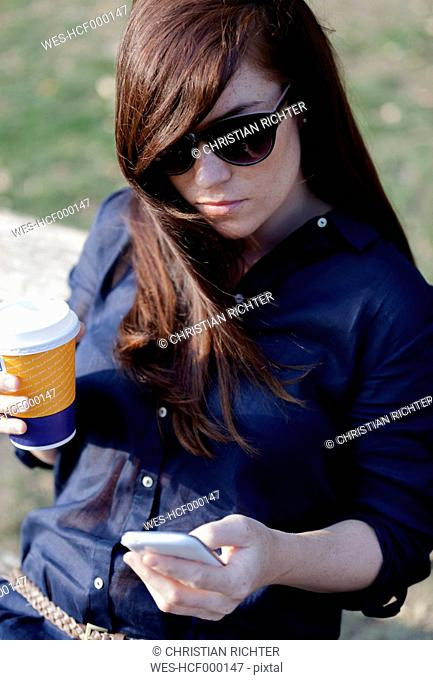 Portrait of woman wearing sunglasses sitting on a park bench with smartphone and coffe to go