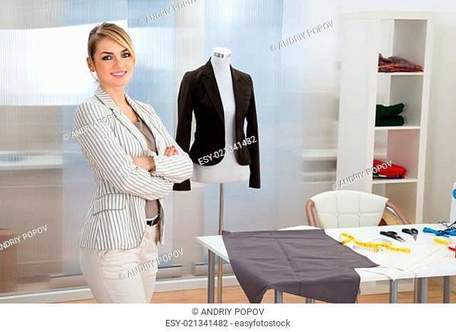 Portrait Of Confident Smiling Fashion Designer In Studio