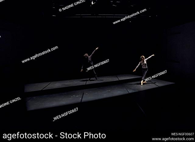 Male and female dancer performing comtemporary ballet on black stage