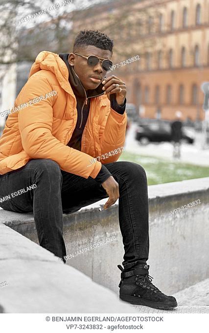 stylish man wearing orange jacket in city, Munich, Germany