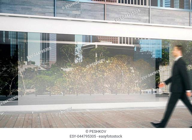 Side view of young businessman walking by shop window during daytime. Ad concept. Mock up, 3D Rendering