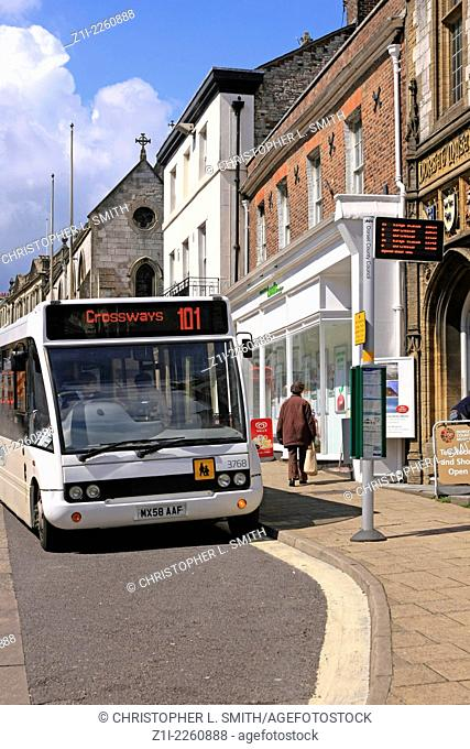 Local Public transport in Dorchester waits at a bus stop for off loading passengers