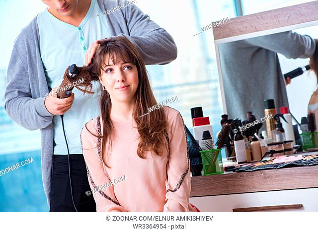Man stylist working with woman in beauty salon