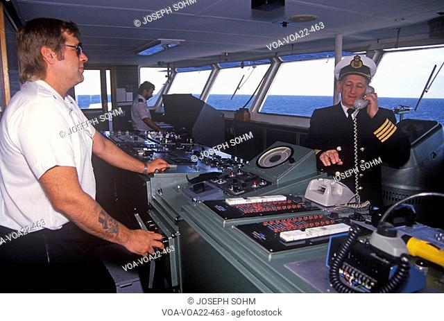 The captain of the ferry Bluenose speaking on the bridge phone while a crew member navigates the boat, Yarmouth, Nova Scotia