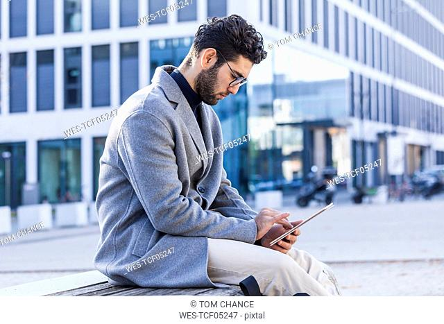 Young man sitting on bench using mini tablet